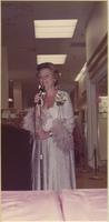 Patricia Stevens speaks into a microphone as fashion commentator during a spring bridal showing at Indian Springs Shopping Center