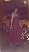 African American London House Model wears a maroon full-length dress during the hot rod and custom auto show