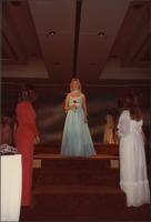 contestant wears an aqua evening gown during the evening gown portion of the Miss Kansas USA 1983 pageant