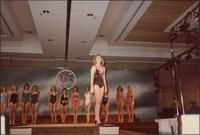 contestant in the Miss Kansas USA 1983 pageant wears a black swimsuit with a dark pink ruffle around the neckline