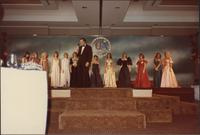 master of ceremonies stands on stage with twelve candidates in evening gowns during the Miss Kansas 1983 USA pageant