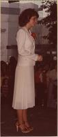 contestant from her right side wearing a white suit as she stands on stage during Show-a-rama