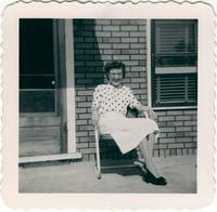 Older woman in a polka dot shirt seated on a front porch