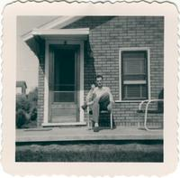 Warren Durrett seated on a front porch
