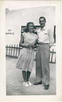 Warren Durrett with a woman in front of a Bar-B-Q restaurant