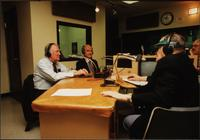 Walt Bodine, Edwin Meese, George McGovern, and one unidentified man conduct an episode of The Walt Bodine Show on KCUR in the studio