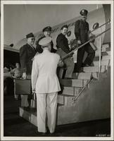 Four men ascend the steps to a transport plane