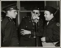 Ted Malone, Capt. Worth, and Major Robert Mc Andrews speak into a microphone