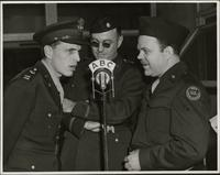 Maj. Robert McAndrews speaks into the microphone as Capt. Worth and Ted Malone look on