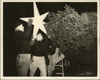 Five men begin decorations by placing the star