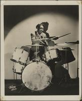 Helen Cole poses as she plays a drum set