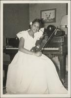 woman smiles as she sits at a piano holding a violin