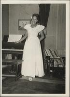 woman smiles as she stands by a piano