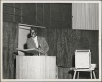 smiling man stands behind a podium