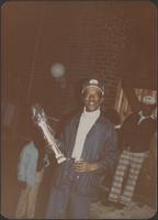man grins as he holds a trophy