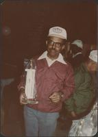 man in a burgundy jacket holds a trophy