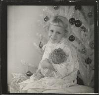 Girl with doll by a Christmas tree