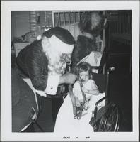 Santa holding out his sleigh bells to young girl