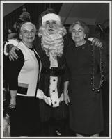 Santa posing for a photo with Margaret Weaver and another woman