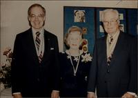 Martha Jane Starr, John W. Starr, and an unidentified man stand with ribbons around their necks