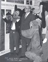 L. Perry Cookingham standing with Disney characters in front of People to People Exhibit