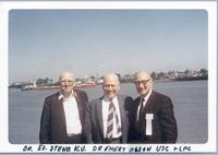 Ed Stene, Dr. Emery Olson, and L. Perry Cookingham pose in front of unknown waterway