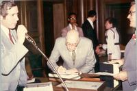 Richard Berkley standing behind a microphone while L. Perry Cookingham signs a piece of paper