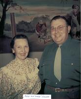 "Alice & ""Hubie"" Edwards in Western wear stand in front of painted mural"