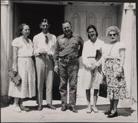 Mr. and Mrs. Lathrop Backstrom, and Harriette W. Cookingham stand in front of unidentified doorway