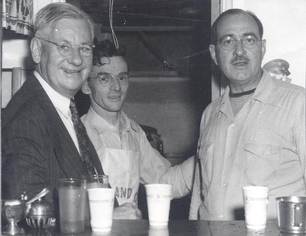 L  Perry Cookingham with unidentified persons behind cup laden bar