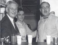 L. Perry Cookingham with unidentified persons behind cup laden bar