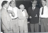 L. Perry Cookingham wearing cowboy hat talking with unidentified persons