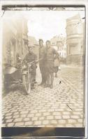 Three men in uniforms, one sits on Motorcycle with sidecar