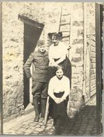 Unidentified man in uniform stands with two unidentified women sitting on ladder