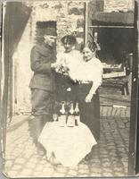 Unidentified man stands with two unidentified women with wine glasses