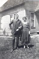 George and Hazel Cookingham besides a house