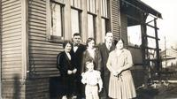 Harriette W., George, Hazel, Clark, L. Perry Cookingham, and Mame Gordinier all in formal clothes stand besides house