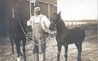Grant Gordinier in front of barn with two horses
