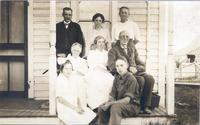 Joseph and Ella Cookingham pose on front porch with unidentified persons