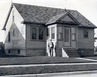 Cookingham stands in front of one story house