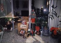 Christmas decorations, presents in a wicker chair, and Christmas tree in sunroom at Starr Residence