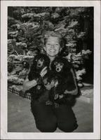 Unknown woman holding two miniature poodles in front of Christmas Tree