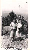 Ferol Koerper and Harriette stand on hill side with rock outcropping that has American flag on a flagpole