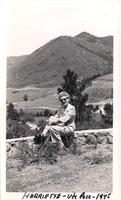 Harriette sits on rock wall with the valley of Ute pass behind her