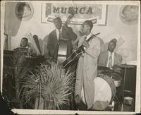 "Jay McShann, Clarence ""Big""; Miller, Eugene ""Jeep"" Griddine, and an unidentified man performing"