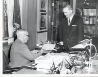 Harry S. Truman signing a sheet of stamps