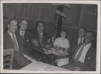 "Buck Clayton seated at a table with, from left to right, Red Richards, Russell ""Big Chief"" Moore, an unidentified girl, Buster Bailey, Kansas Fields"