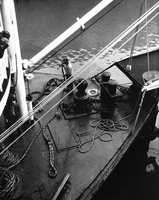 Alone on the foredeck, a hand coils lines under the watchful eye of the mate and passengers.